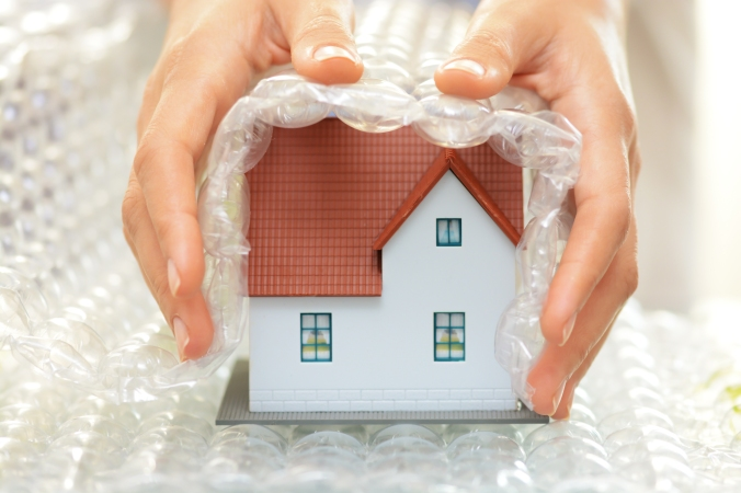 Woman hands covering a model house with bubble wrap
